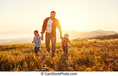 happy family father and children in nature at sunset