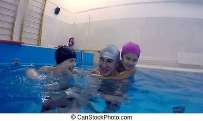 Happy family father and children in the pool jump into the water joy