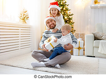 happy family  father and children playing near Christmas tree