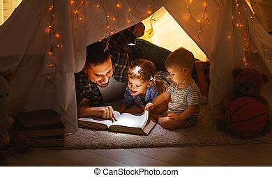 Children boy and girl reading book with flashlight in tent stock happy family father and children reading a book in tent at home sciox Gallery