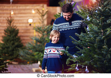 happy family, father and son buying a christmas tree for winter holidays at seasonal market