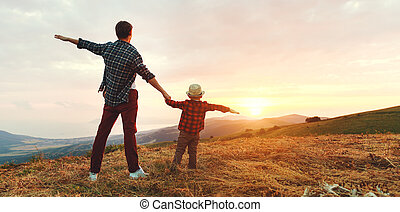 happy family father and son in nature at sunset