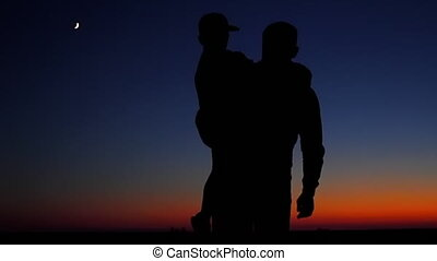 Happy family: father and son see off the sun. Silhouettes....