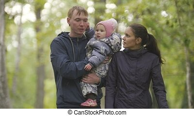 Happy family: Father, Mother and child - little girl in autumn park: walking through the alley with the fallen leaves, close up
