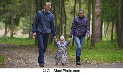 Happy family: Father, Mother and child - little girl in autumn park: walking through the alley with the fallen leaves
