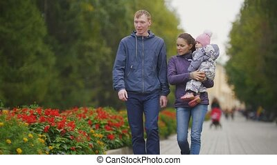 Happy family: Father, Mother and child - little girl in autumn park: walks in the alley with flowers