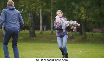 Happy family: Father, Mother and child - little girl walking in autumn park: running and playing at the grass