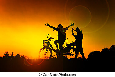 Happy Family, father, mother and daughter with bicycle at sunset