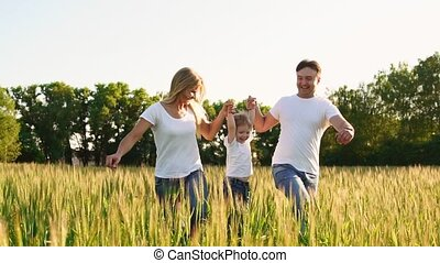 Happy family: Father, mother and son, running in the field dressed in white t-shirts