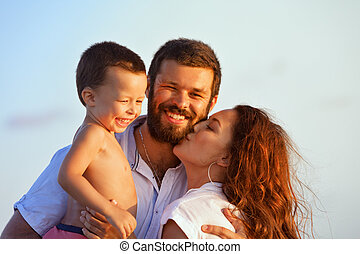 Happy family - father, mother, baby on sunset beach