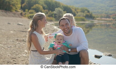 Happy family filled with love sitting on a background of lake and forest