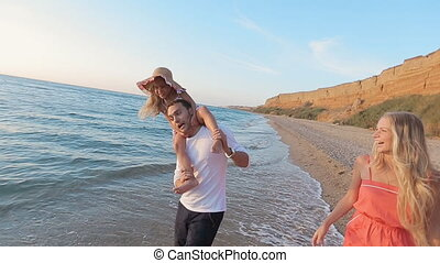 Happy family fooling around while walking along the seashore