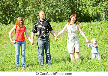 family from four stands on grass