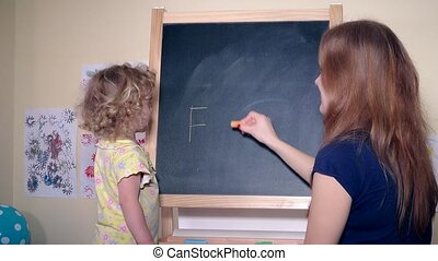 Happy family girls mom and daughter writing word father on black chalk board