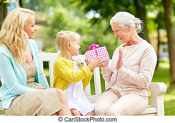 happy family giving present to grandmother at park