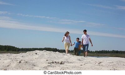 Happy family goes on sand