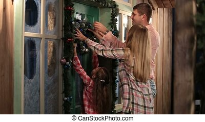 Happy family hanging Christmas wreath on the door