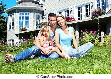 Happy smiling family near new house. Realty.