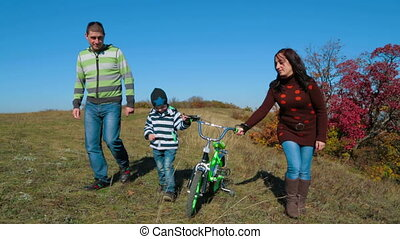 Happy Family Having A Promenade In Autumn Meadow