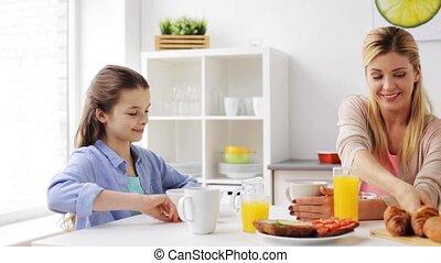 happy family having breakfast at home kitchen