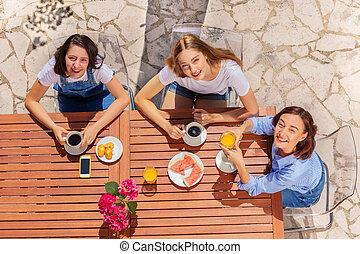 Happy family having breakfast at street cafe