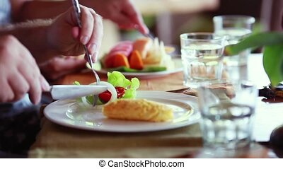 Happy family having breakfast omelet with fruit salad and...