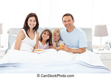 Happy family having breakfast together on the bed at home