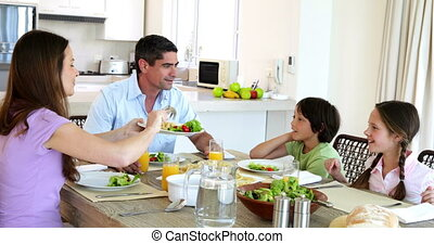 Happy family having dinner together at home in the kitchen