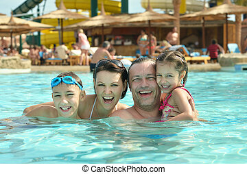 family having fun - Happy family having fun in pool with...