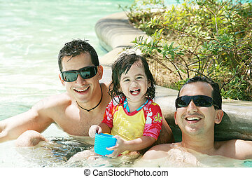 Happy family having fun in swimming pool. Brothers and niece having fun in the pool on summer vacation