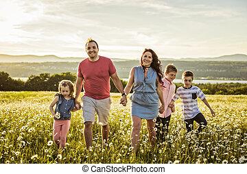 Happy family having fun on daisy field at sunset