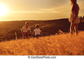 Happy family having fun playing at sunset.
