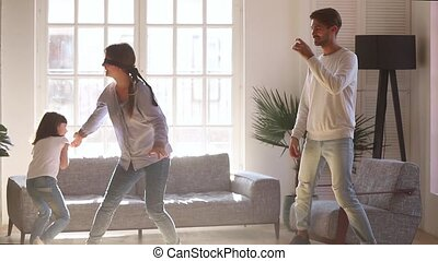 Happy family having fun laughing playing tag touch hide and seek game in living room, blindfolded mom catching child daughter and dad at home, young parents with kid girl enjoy activity together