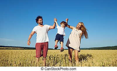 Happy family having fun playing in the field .