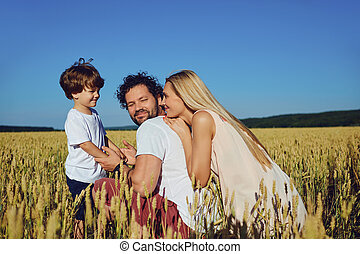 Happy family having fun playing in the field.