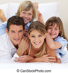 Happy family having fun together lying on a bed