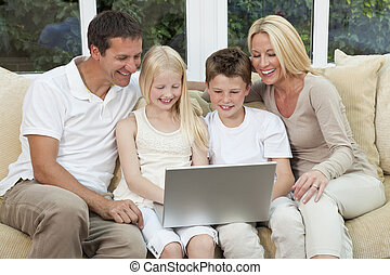 Happy Family Having Fun Using A Computer At Home