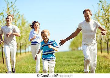 Happy family having fun walking in the garden in spring, summer.
