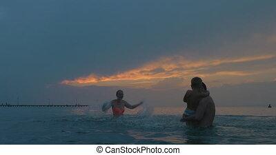 Happy family having fun with splashing water