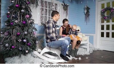 Happy family having fun with the baby in the winter scenery