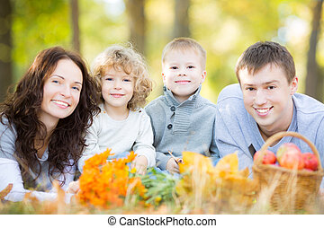 Happy family having picnic in autumn park