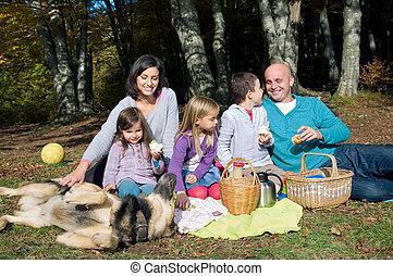 Happy family having picnic in autumn