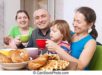 Happy family having tea at home