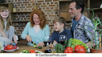 Happy Family Help Mother To Cook Dinner Together In Kitchen Parents With Two Children Talking Preparing Food At Home