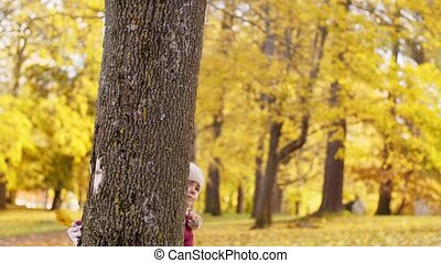 happy family hiding behind tree at autumn park - family,...