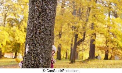 happy family hiding behind tree at autumn park