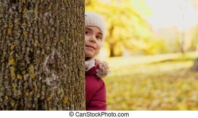 happy family hiding behind tree at autumn park - family,...