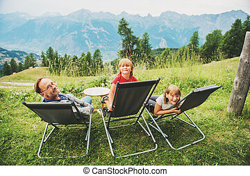 Happy family hiking in swiss Alps, enjoying amazing view, travel with kids. Image taken in canton of Valais, Switzerland