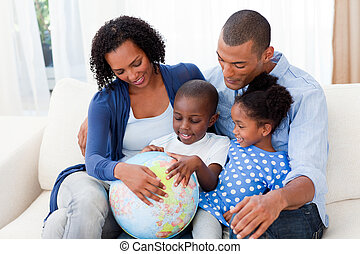 Happy family holding a terrestrial globe on the sofa