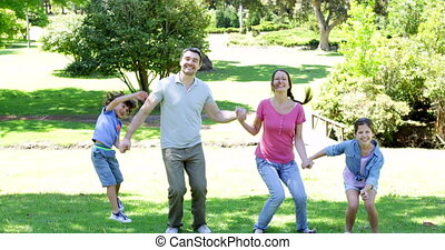 Happy family holding hands and jumping on a sunny day
